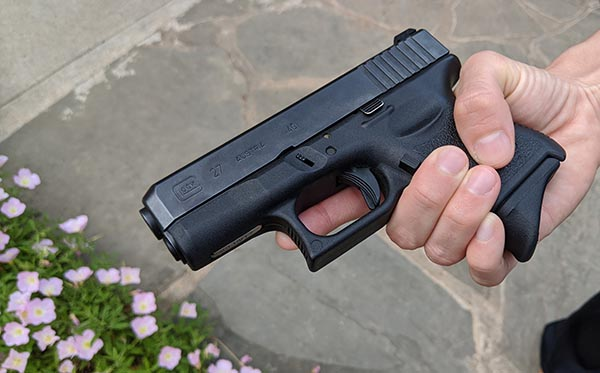 glock 27 in small female hands, extended grip on magazine